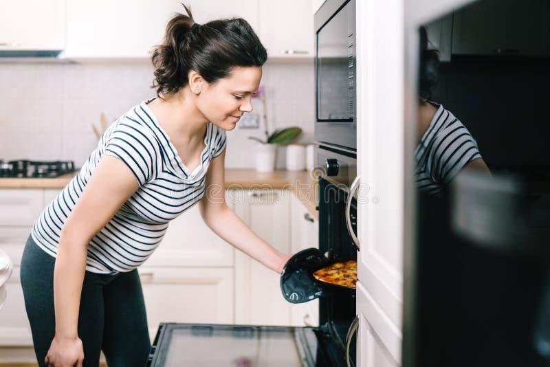 Porträt der schönen schwangeren Frau, die Pizza zubereitet und Abendessen kocht lizenzfreie stockfotografie
