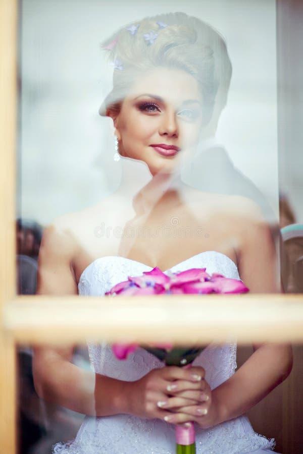Porträt der schönen sexy Brautblondine in einem weißen Kleid mit PU lizenzfreies stockfoto