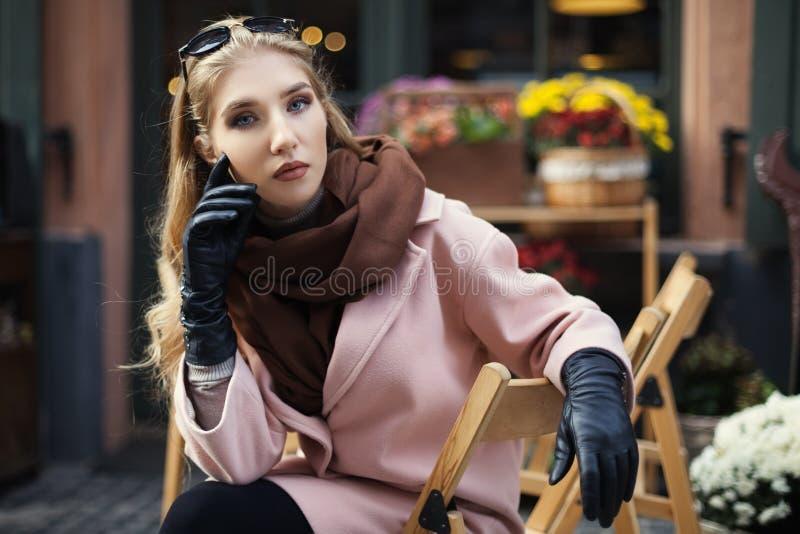 Porträt der schönen stilvollen jungen Frau, die im Straßencafé sitzt Vorbildliches Looking an der Kamera Abschluss oben Junge Fra lizenzfreie stockfotografie