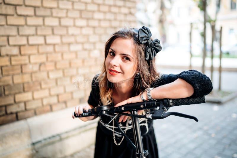 Porträt der schönen und attraktiven lächelnden Frau, die modernen Stadttransport mit elektrischem Roller reitet lizenzfreies stockbild