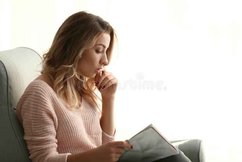 Porträt der schönen Zeitschrift der jungen Frau Lesezu hause lizenzfreies stockbild