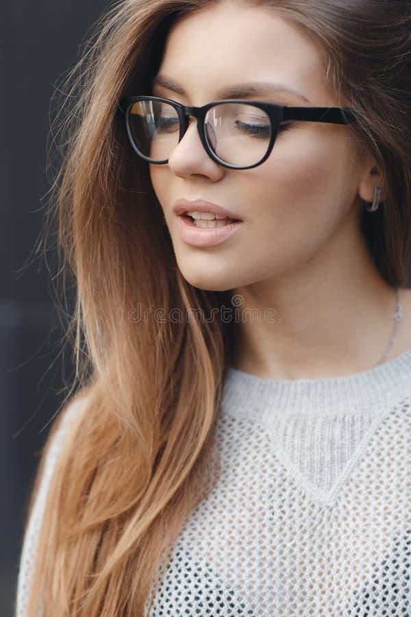 Porträt der Schönheit in den Gläsern auf grauem Hintergrund lizenzfreie stockfotos
