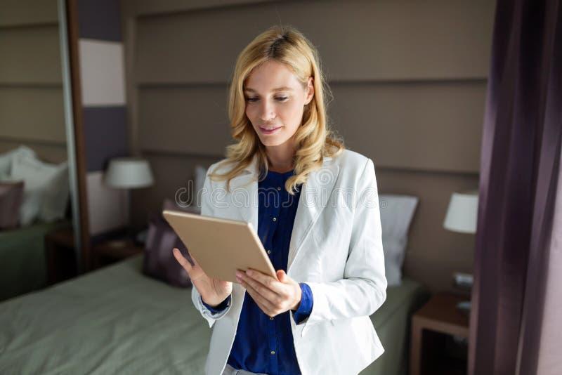 Porträt der Schönheit, die Tablette im Schlafzimmer verwendet stockfotos