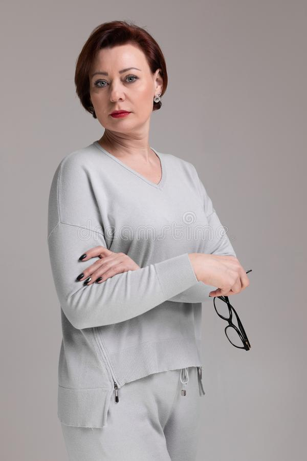 Porträt der Schönheit in der hellen Kleidung mit den Gläsern in der Hand lokalisiert auf hellem Hintergrund stockbild