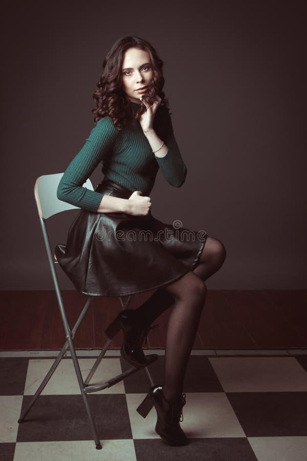 Porträt der Schönheit mit Make-up, auf einem Stuhl, in der grünen Strickjacke und schwarzen im Lederrock, die auf dunklem Schokol lizenzfreie stockfotografie