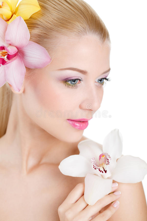 Porträt der Schönheit mit Orchideen-Blume in ihrem Haar. Schönes vorbildliches Woman Face. Perfekte Haut. Berufs-Make-up.Makeup. lizenzfreies stockfoto