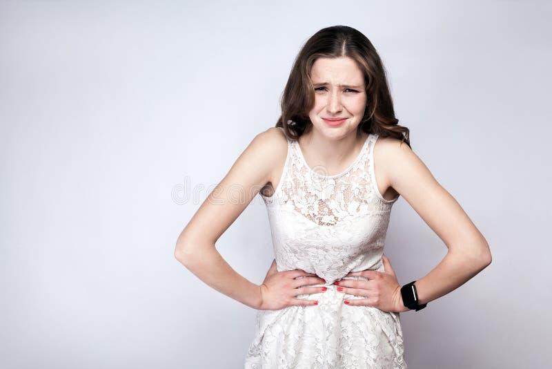 Porträt der Schönheit mit Sommersprossen und Weißkleid und intelligente Uhr mit Magenschmerzen auf Hintergrund des silbernen Grau lizenzfreie stockfotografie