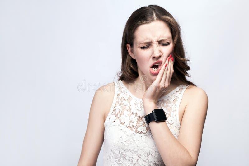 Porträt der Schönheit mit Sommersprossen und Weißkleid und intelligente Uhr mit den Zahnschmerz auf Hintergrund des silbernen Gra stockfoto