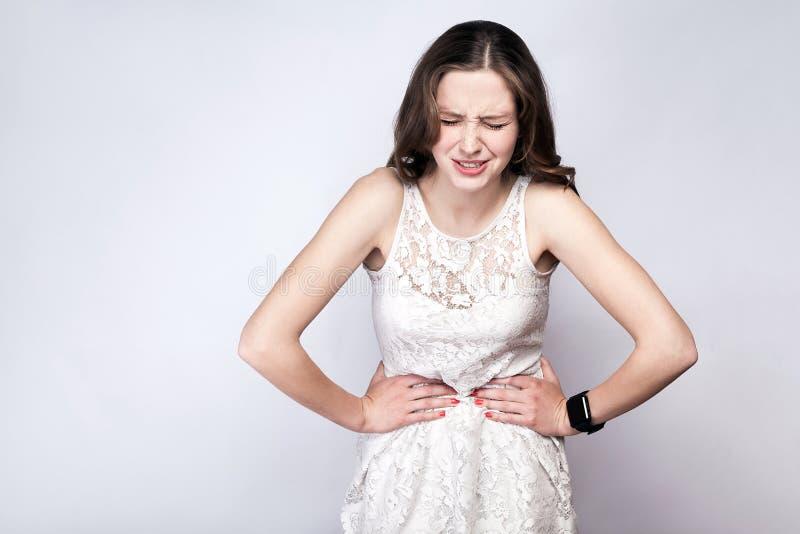 Porträt der Schönheit mit Sommersprossen und Weißkleid und intelligente Uhr mit Magenschmerzen auf Hintergrund des silbernen Grau lizenzfreie stockfotos