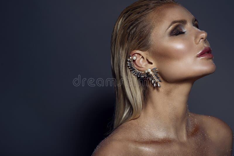 Porträt der schicken herrlichen blonden Frau mit dem nassen Haar, künstlerischem funkelndem Make-up und der Stulpe auf ihrem Ohr stockbild