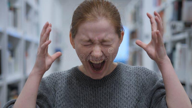 Porträt der schreienden jungen Frau, schreiend im Café stockfoto