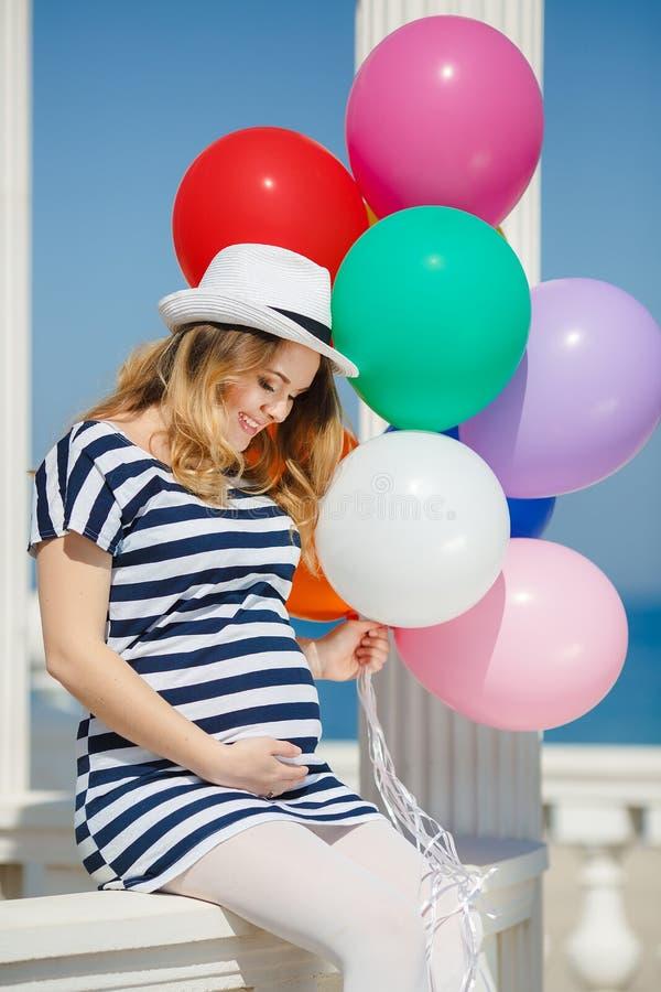 Porträt der schwangeren Frau mit Sonnenbrille und Hut lizenzfreie stockfotografie