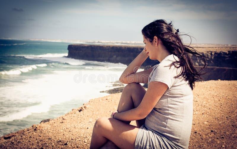 Porträt der schwangeren Frau sitzend an der Strandküste stockfotografie