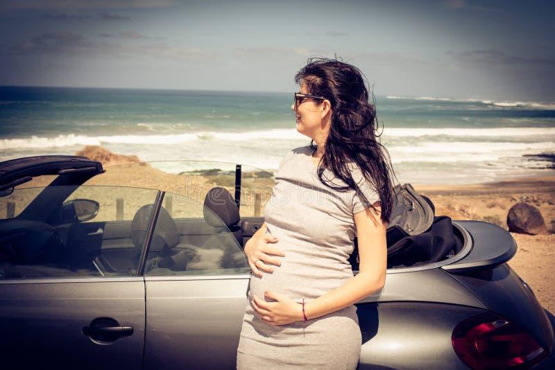 Porträt der schwangeren Frau am Strand lizenzfreies stockbild