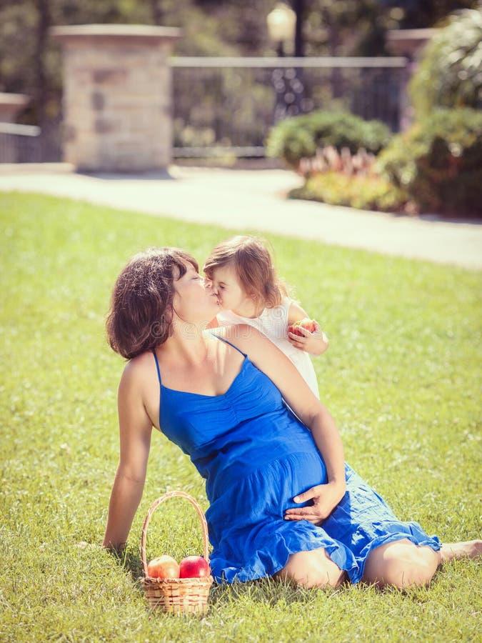 Porträt der schwangeren Mutter und der Tochter, die draußen spielen umarmt lizenzfreie stockfotografie