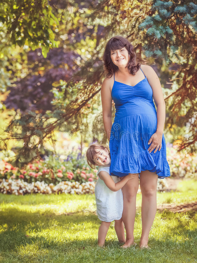 Porträt der schwangeren Mutter und der Tochter, die draußen spielen umarmt lizenzfreies stockbild