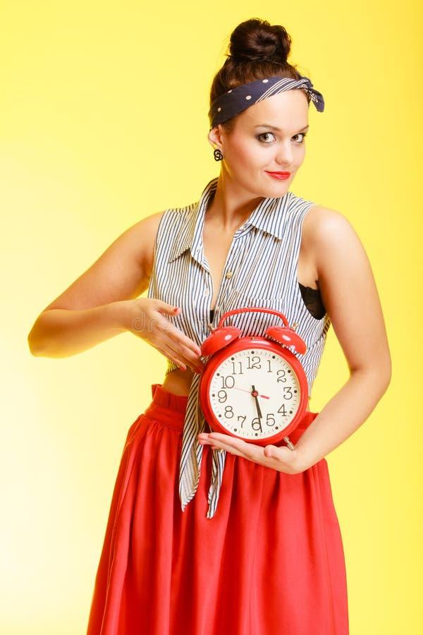 Porträt der sexy Frau des modernen Pin-up-Girl, die rote Uhr hält stockbild