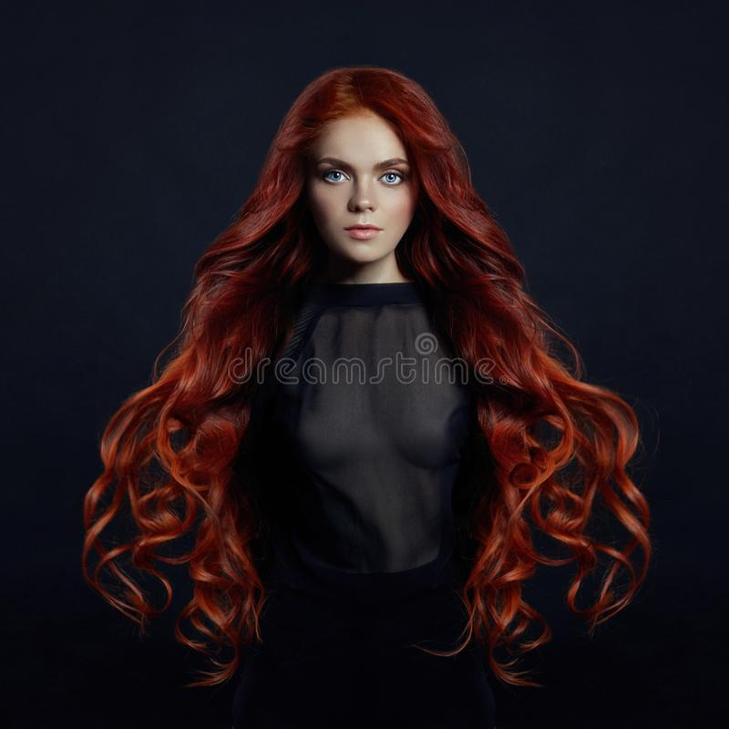 Porträt der sexy Frau der Rothaarigen mit dem langen Haar auf schwarzem backgroun lizenzfreies stockbild
