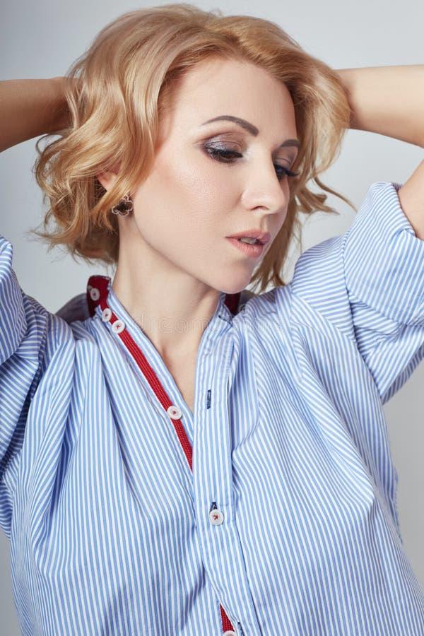 Porträt der sexy Geschäftsfraublondine im blauen Hemd, bloßer Körper, stockfotografie