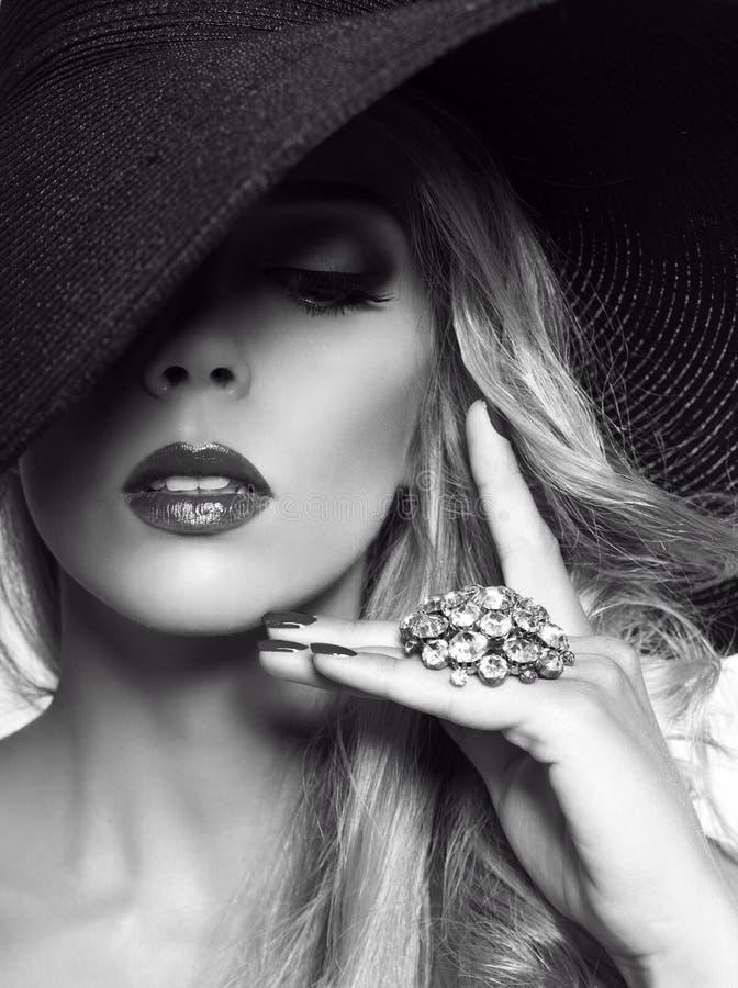 Porträt der sexy schönen blonden Frau im schwarzen Hut mit Ring lizenzfreies stockfoto