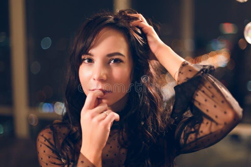 Porträt der sinnlichen jungen Frau in der schwarzen Spitzekleiderstellung vor Fenster lizenzfreie stockbilder