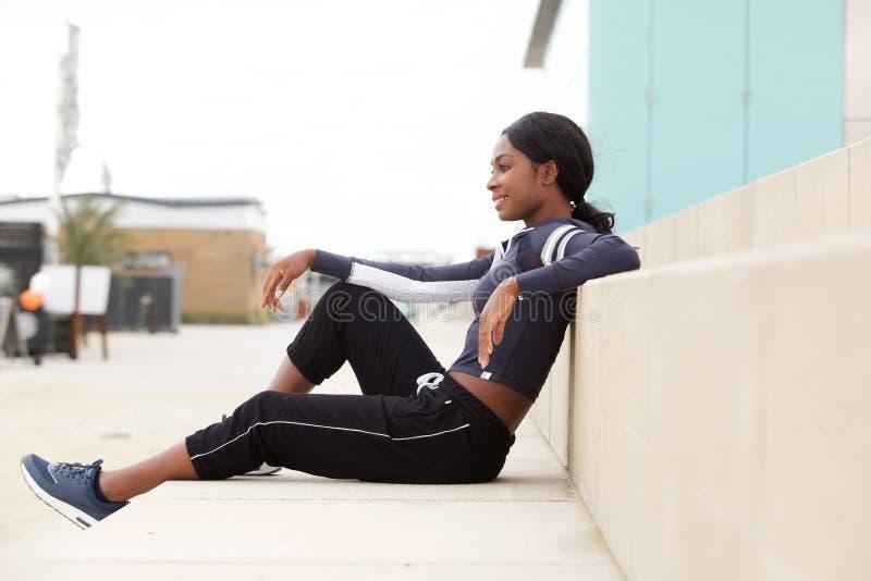 Porträt der sitzenden Außenseite der geeigneten jungen Afroamerikanersport-Frau lizenzfreies stockbild
