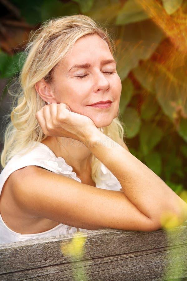 Porträt der sitzenden Außenseite und des Genießens der Blondine der Sonne lizenzfreie stockbilder