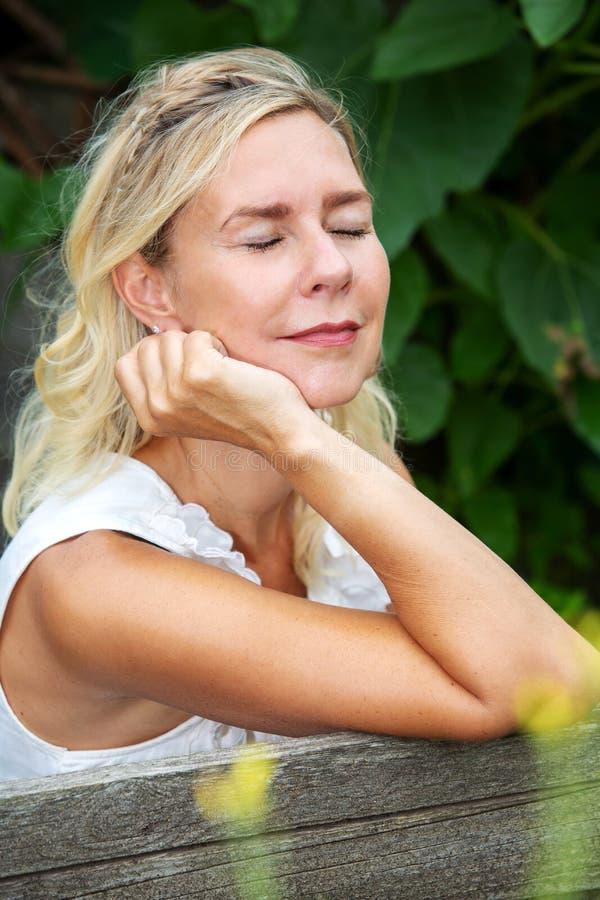 Porträt der sitzenden Außenseite und des Genießens der Blondine der Sonne lizenzfreies stockbild