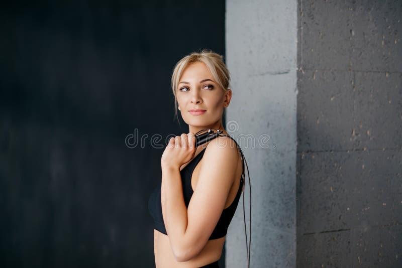 Porträt der Sportfrau mit Springseil auf seiner Schulter stockbild
