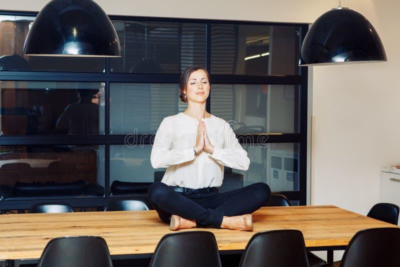 Porträt der sportlichen jungen weißen kaukasischen Geschäftsfrau des dünnen Sitzes, die meditiert, Yoga tuend, trainiert lizenzfreies stockbild