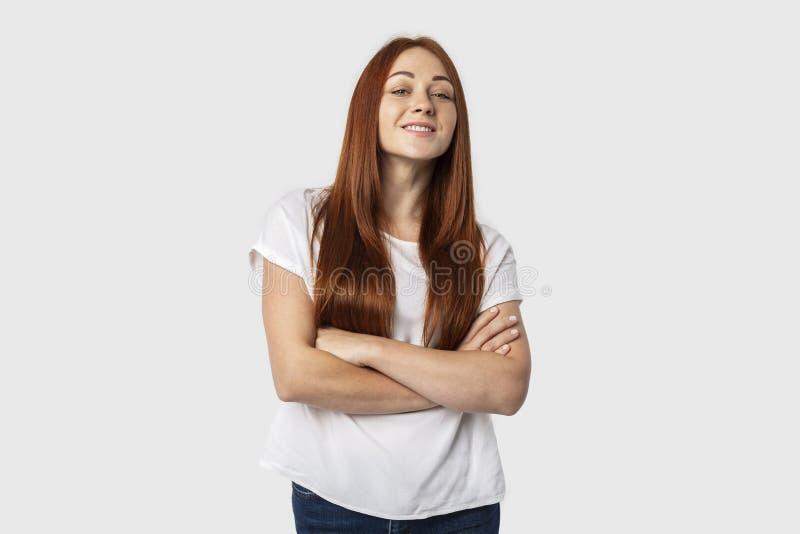 Porträt der Stellung der jungen Frau mit den gekreuzten Armen lokalisiert auf grauem Hintergrund mit freundlichem Lächeln stockfotografie