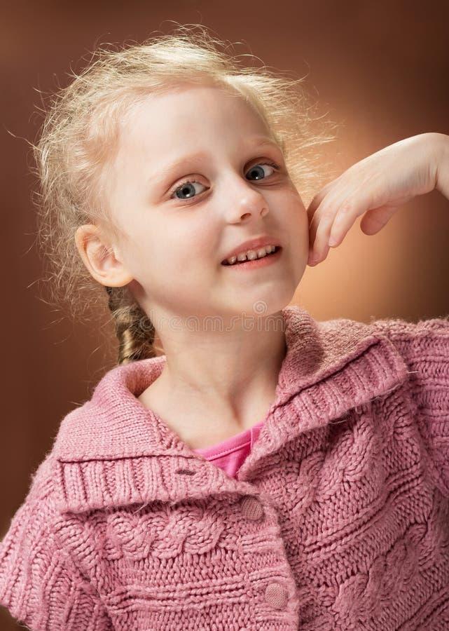 Porträt der Taille des lächelnden kleinen blonden Mädchens auf dem Wurzelhintergrund stockbild