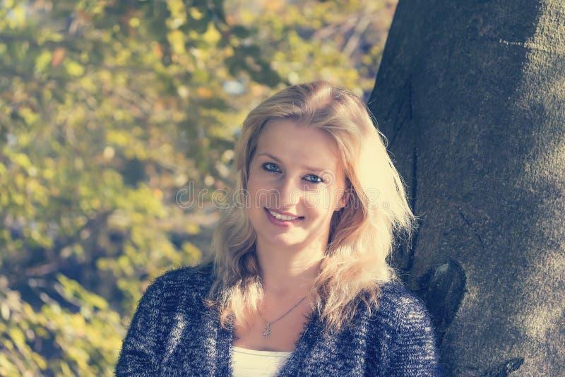 Porträt der toothy lächelnden jungen blonden Frau draußen stockbilder