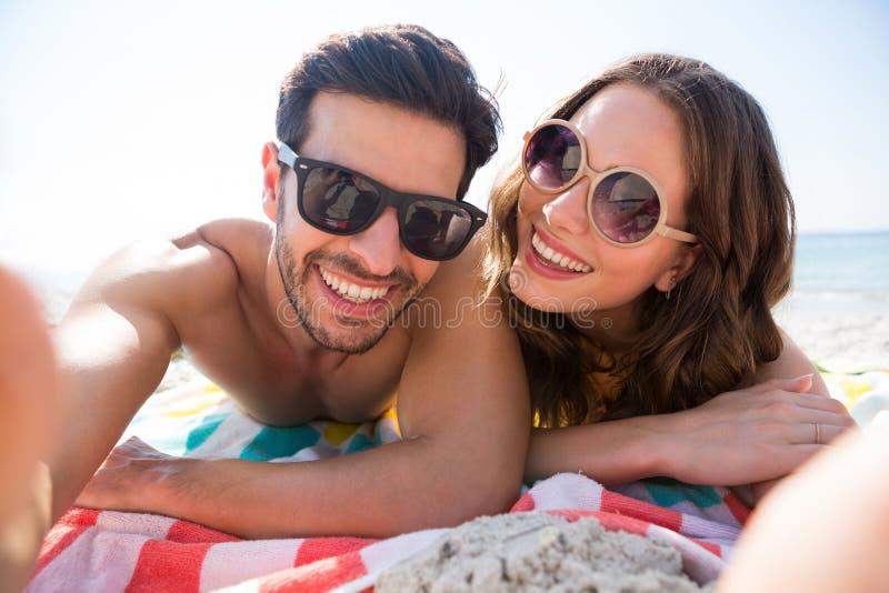 Porträt der tragenden Sonnenbrille des glücklichen Paars beim auf Decke am Strand zusammen liegen lizenzfreie stockbilder
