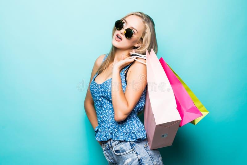 Porträt der tragenden Sonnenbrille eines aufgeregten schönen Mädchens, die Einkaufstaschen lokalisiert über blauem Hintergrund hä lizenzfreie stockfotos