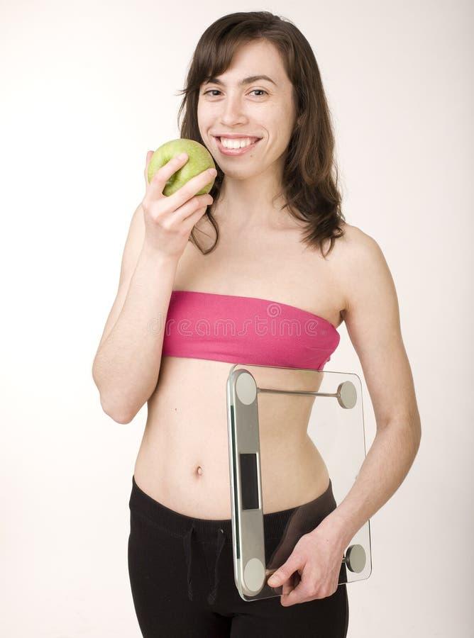 Porträt der tragenden Sportkleidung des hübschen Mädchens, die Skalen halten und des messenden Bands mit grünem Apfel lizenzfreie stockfotos
