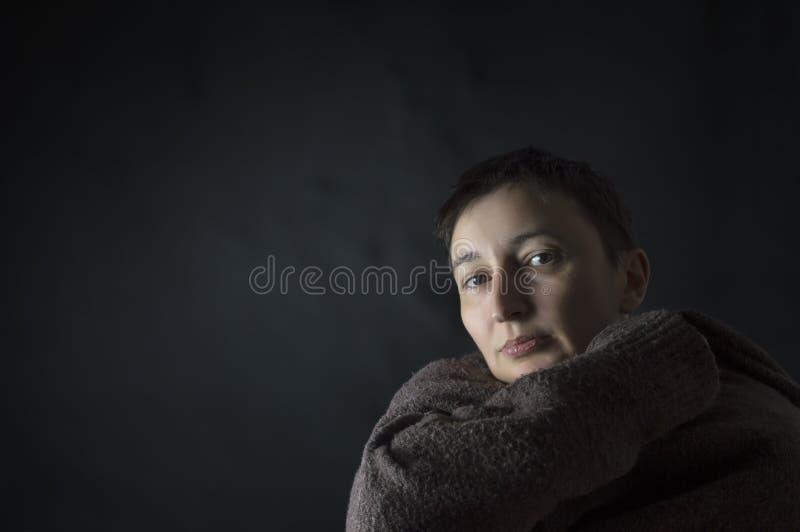 Porträt der traurigen, deprimierten Frau, die allein sitzt stockfotografie