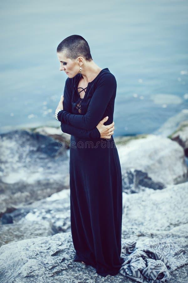 Porträt der traurigen schönen kaukasischen weißen jungen kahlen Mädchenfrau mit dem rasierten bereitstehenden Wasserhauptsee des  lizenzfreie stockfotografie