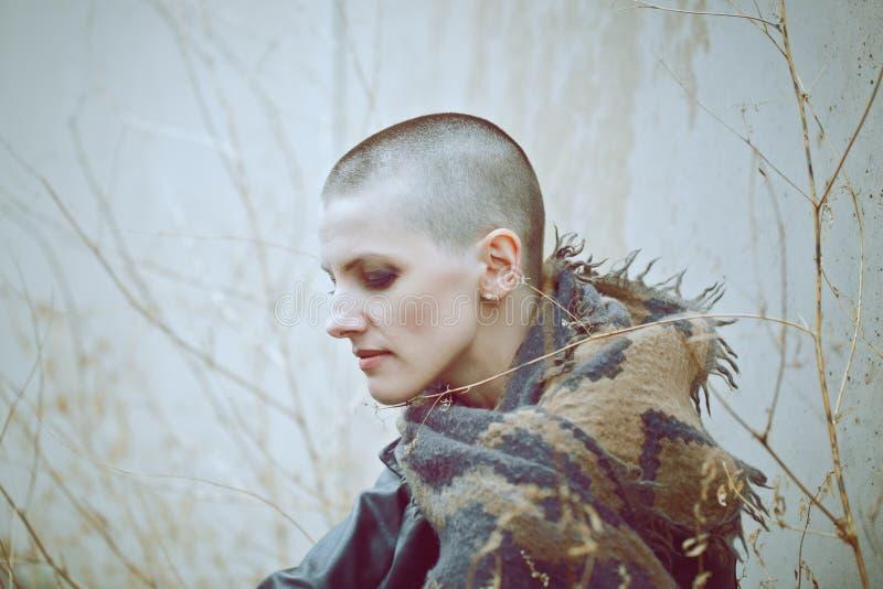 Porträt der traurigen schönen kaukasischen weißen jungen kahlen Mädchenfrau mit rasiertem Haarkopf in der Lederjacke und im Schal lizenzfreies stockbild