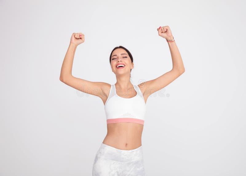 Porträt der Turnhallenfrau feiernd mit den Händen in der Luft stockfoto