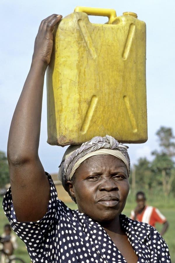 Porträt der Ugandanfrau mit Benzinkanister auf Kopf lizenzfreies stockfoto
