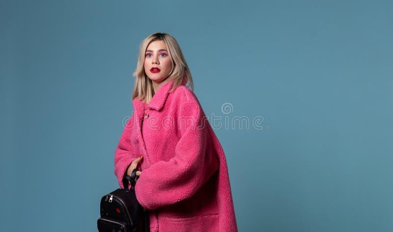 Porträt der ungewissen shoked attraktiven blonden Frau mit Rucksack in den Händen stockfoto