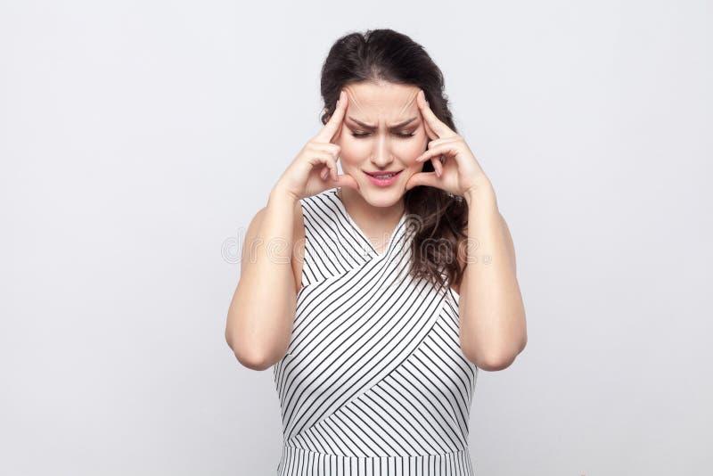 Porträt der unglücklichen traurigen schönen jungen brunette Frau mit Make-up und gestreifter Kleiderstellung, Kopf mit Kopfschmer lizenzfreies stockfoto