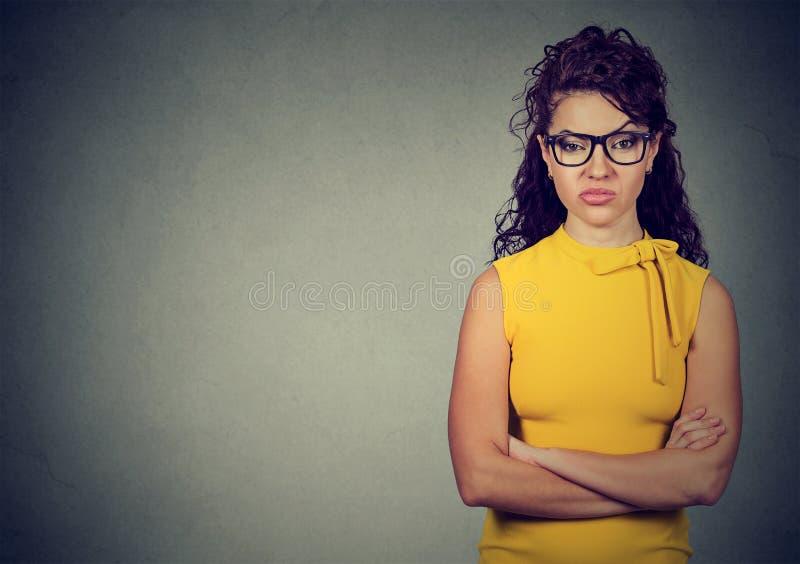 Porträt der verärgerten Frau im gelben Kleid, das mit den Armen gefaltet steht stockbild