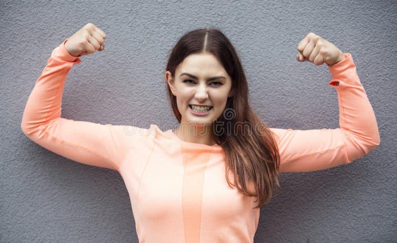 Porträt der Vertretung der jungen Frau ihrer Muskeln lizenzfreies stockfoto