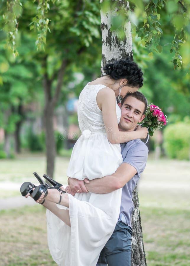Porträt der weiblichen Braut der schönen jungen Paare und der Mannesbräutigam, der im Sommer umarmt, parken Frauenfrau und -blick lizenzfreies stockbild
