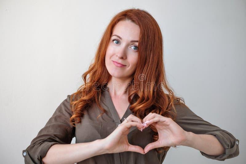 Porträt der yappy kaukasischen Frau, die Herz mit den Fingern hält stockfotos