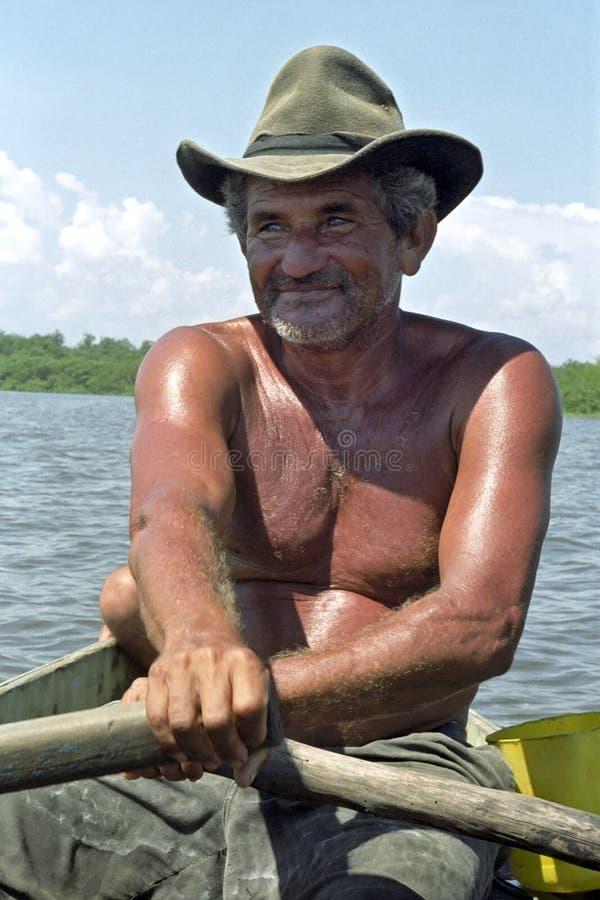 Porträt des älteren Fischers sein Boot rudernd lizenzfreie stockfotografie