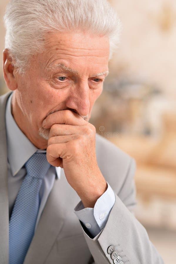 Porträt des älteren Geschäftsmannes, der zu Hause denkt stockfoto