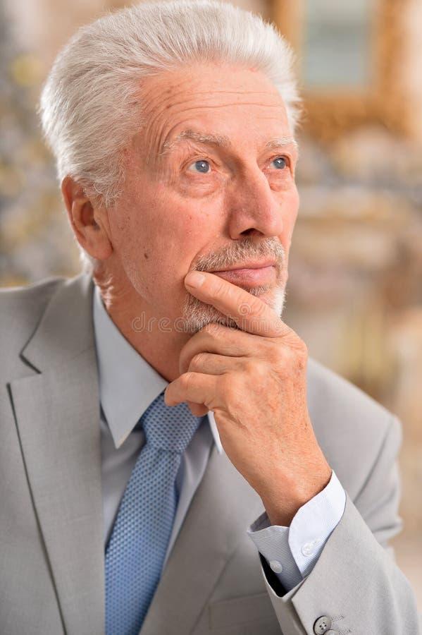 Porträt des älteren Geschäftsmannes, der zu Hause denkt stockbild